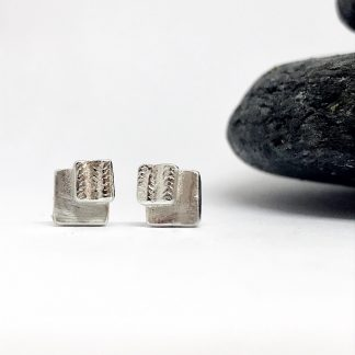 tiny double square silver earrings next to a grey slate stone on a white background