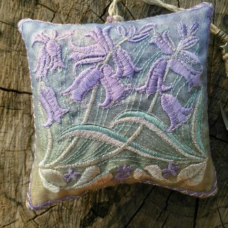 A pastel lilac coloured design of Bluebell flowers features on this lavender bag shown displayed on a weathered log