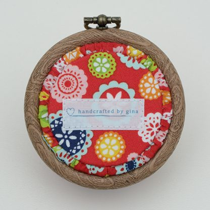 Flower pin cushion in red fabric with geometric flowers