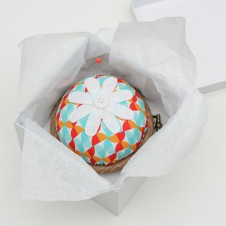 Flower pin cushion in red and turquoise geometric fabric