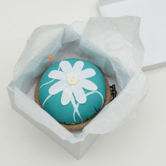 Flower pin cushion in abstract teal fabric