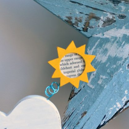 Yellow sun on wire attached to a white wooden cloud sitting on a shelf in front of a blue star