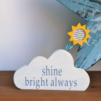 White wooden cloud with a sun to the top sitting on a shelf in front of a blue star