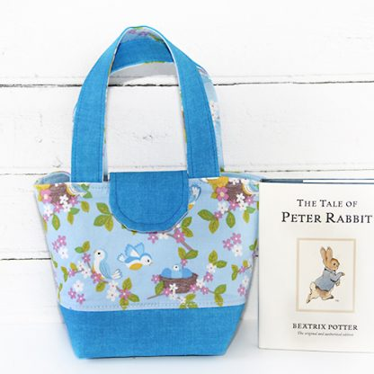 Blue toy tote beside book