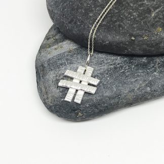 Textured sterling silver hashtag pendant on a sterling silver chain laid out on grey slate stones
