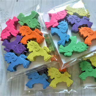 Pastel coloured selection of wax crayon unicorns in packaging
