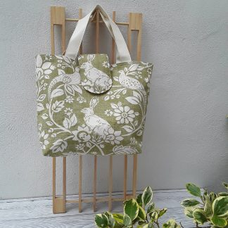 Handbag in cream hares on green 0rint fabric, magnetic tab fastening.