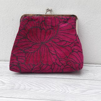 Hand held clutch bag in deep, pink, embossed velvet with shing chrome frame and clasp fastening.