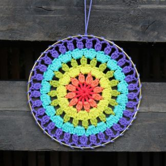 crochet rainbow mandala attached to a brass ring
