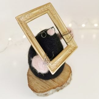sculpture of a mole wearing spectacles and holding a picture frame