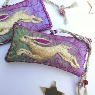 a light golden hare is embroidered onto a rectangular shaped lavender bag made of fabric that changes from a spring green to lilac. there are two of these on a white ground accessorized with a couple of mirrored little stars.