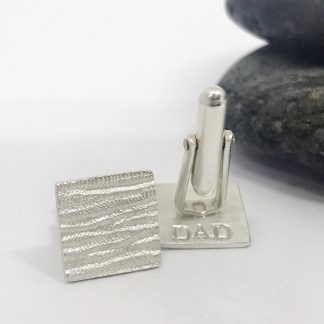 textured square silver cufflinks one with DAD stamped on reverse on a white background next to a grey stone