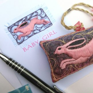 A pink hare is embroidered for a card saying Baby Girl and is next toa similar design as a lavender bag gift. A pen and stamp shows the intention of its use
