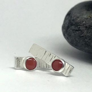 red coral and silver stud earrings on a white background sitting in front of grey slate stones
