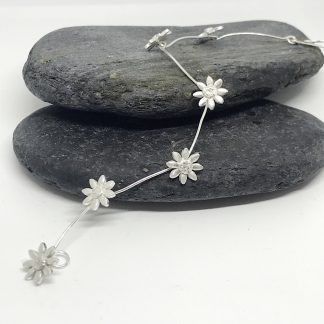 Silver Daisy Chain Bracelet laid across grey slate stones on a white background