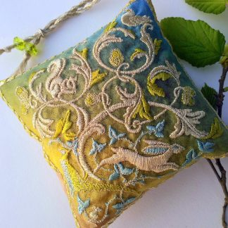A square lavender bag in new bright green spring colours of a Woodland scene with squirrel, hare, pheasant, pidgeon and mouse in gold thread stitches. A leafy twig lies next to the pouch which has beaded loop so it hangs diagonally.