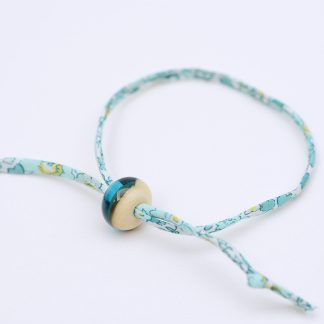 Turquoise liberty cord bracelet with lamp work ivory and turquoise bead