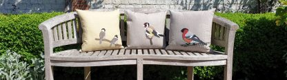 Three Appliqued garden bird cushions on a bench showing Bullfinch, Goldfinch and sparrows