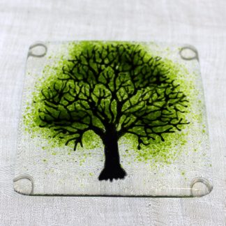 black tree with green leaves in fused glass