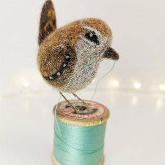 wren sitting on a vintage cotton reel