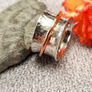 wide silver textured band ring with plain copper thinner spinning ring.