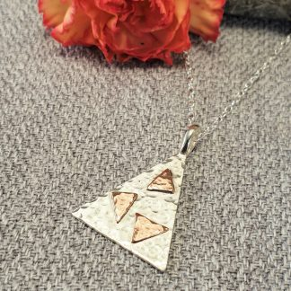 Silver triangle pendant with tumbling triangles of copper on a silver chain