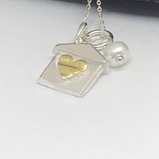 silver house charm with a textured gold heart and freshwater pearl on a white background