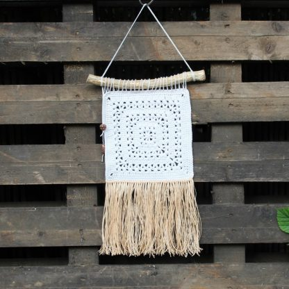 Boho chic wall hanging on a fence