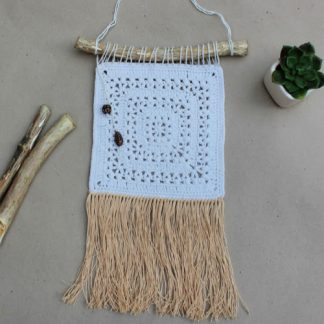 cream wall hanging with linen fringe flat lay with twigs and cacti