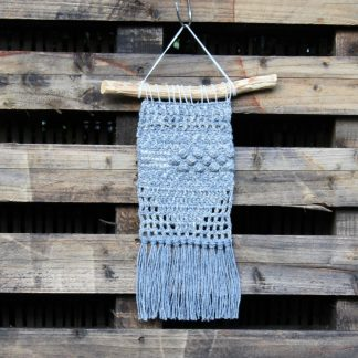 crochet wall hanging in grey hung from a piece of natural wood