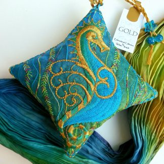 Turquoise blue and gold seahorse embroidery on a small cushion shaped lavender bag with beaded loop arranged with a pleated scarf of similar colours on aplain white back ground with small business label showing