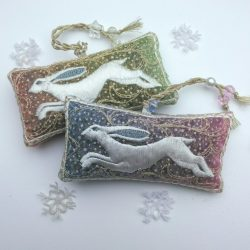 Two embroidered lavender bags lying side by side featuring white running hares on the front and gold twisted braid loops with beads, the fabric changes from one colour to another at each end, using a rainbow changeant fabric