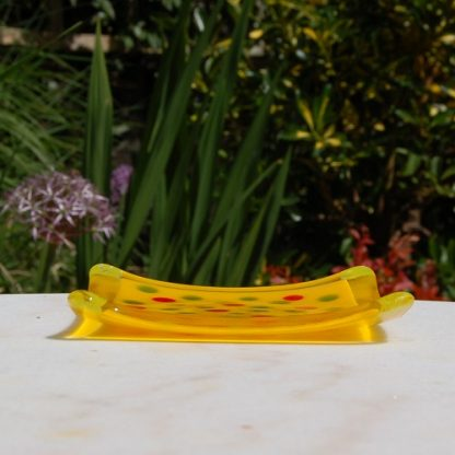 Side view of yellow glass trinket dish with dots of red and green in the centre
