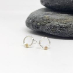 small sterling silver circle earrings with a rose gold sphere sitting on a white background in front of some grey slate stones