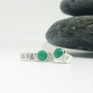 silver earrings with a green gemstone sitting next to grey slate stones on a white background