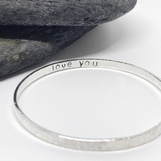 silver childrens bangle with the words love you stamped inside on white base next to grey slate