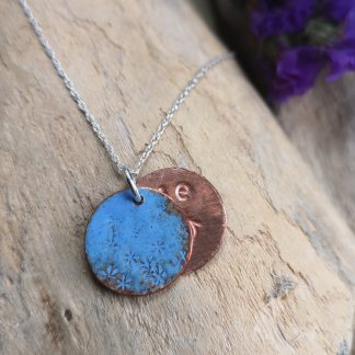 Small handcrafted double copper pendant, top is lavender blue enamel, the other stamped Love U sits behind or can be brought to the front by flipping it over the jump ring. Held on a silver chain.