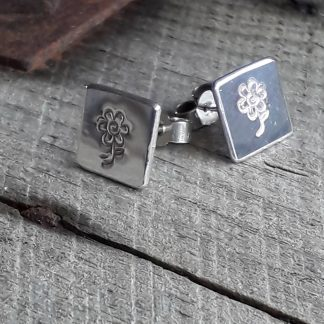 Square stud earrings with a flower stamped in to the surface.