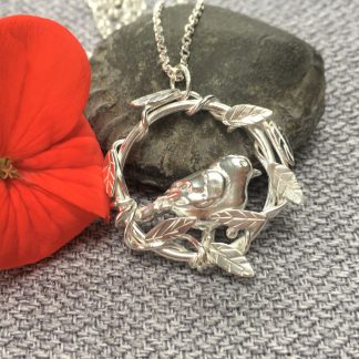 Little silver bird surrounded by a circle of intertwined leaves and vines on a silver chain pendant necklace