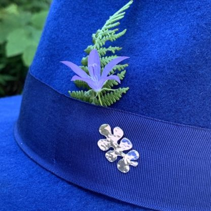 Silver hammered pin on hat