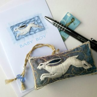 A white Hare features on this blue embroidered lavender pouch with beaded and braided hanging loop.