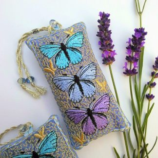 Three blue butterflies in a stack on this small rectangular lavender bag featured next to purple lavender flowers