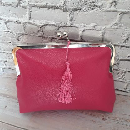 Clutch bag in fuschia pink faux leather with shiny chrome frame, silk removable tassel and zip pocket