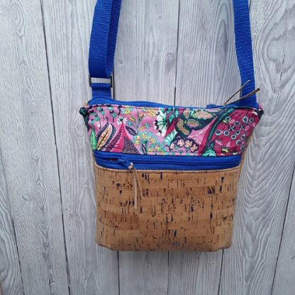 Cross body shoulder bag in natural cork with sparkly blue flecks, two zip pickets and adjustable strap. Medium size