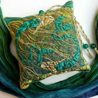 Embroidered design of two fish swimming in opposite directions in jade green colours on a lavender pouch with a scarf laid next to it in similar colours, gold tassels with beads.
