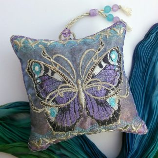 Lilc coloured butterfly embroidered on a square lavender bag with blue crinkled scarf lying next to it on a white back ground.