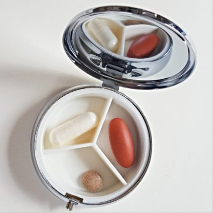 Round pill box open with pills