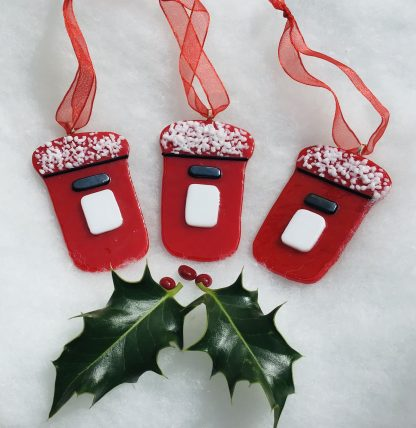 Three red fused glass postboxes with snow