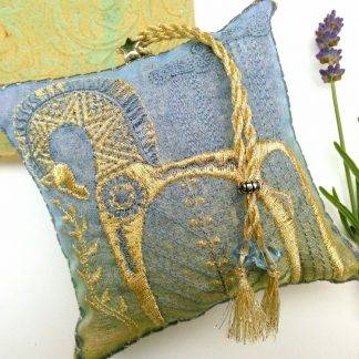 A square cushion shaped lavender bag with gold embroidery of a trojan horse, with beaded tassel on a white back ground and a single lavender flower at the side