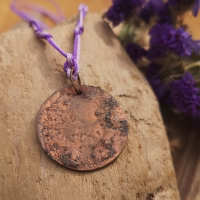 """Handmade by Tamala presents Crystal Clear Moon. It's copper forged with fire and held on a purple and lilac adjustable cord. Length at it's shortest is 15"""" at it's longest 26"""". The pendant is 25mm. Clear quartz beads finish the cord adding a lovely detail"""